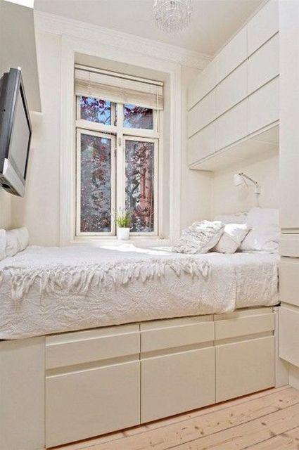 Quarto de casal pequeno e claro com cama embutida no roupeiro e encostada na parede. A cama também possui gavetas.