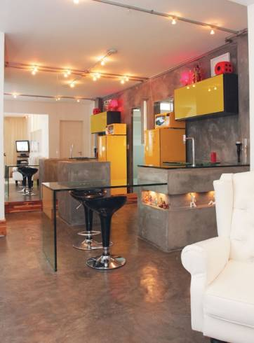 Cozinha com piso de Cimento queimado e armários amarelos