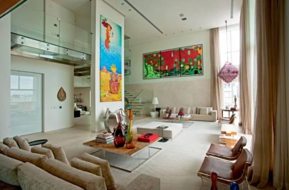 Decoração de sala com pé direito duplo com obras de arte