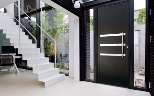 porta pivotante preta em casa com paredes de vidro