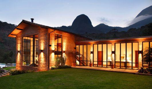 casa moderna rústica no campo com janelas altas e tijolos aparentes