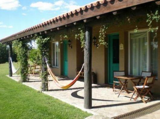 varanda com rede de descanso e colunas com plantas trepadeiras