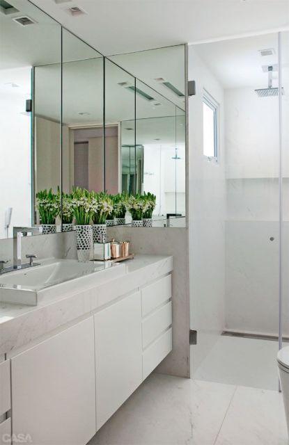 banheiro com decoração clean e uso de espelhos
