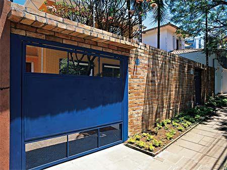 muro de tijolo à vista com portão azul