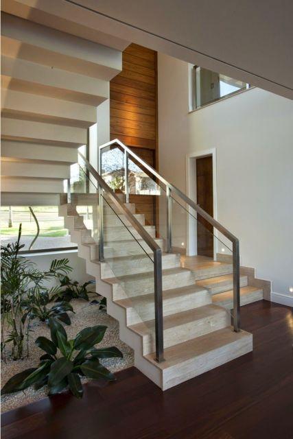 escada jardim embaixo:porta e parede de madeira combinam com o piso de mesmo material