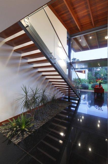 escada jardim embaixo:parede de vidro é tendência e permite a entrada da luz natural