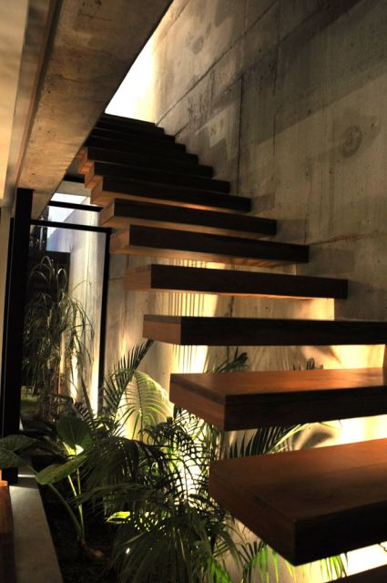escada jardim embaixo:parede de cimento queimado tem traços mais industriais, mas a ideia