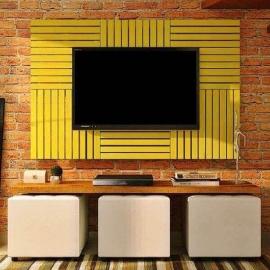 Painel de pallet amarelo grande sobre parede de tijolos laranjas. Abaixo, três puffs brancos sob uma prateleira de madeira.