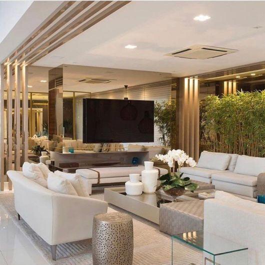 Sala elegante com sofás brancos e painel de tv de espelho bronze