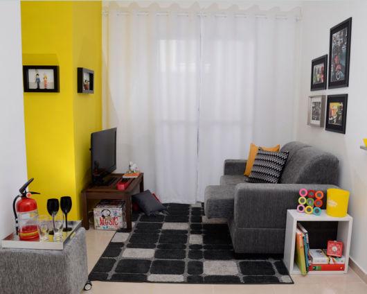 Sala De Estar Cinza Com Amarelo ~  apoiados no chão; Livros decorando a mesa de centro e de canto