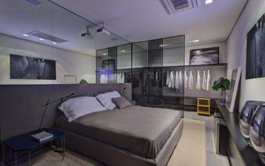 quarto com divisória de vidro e espelho em toda a parede