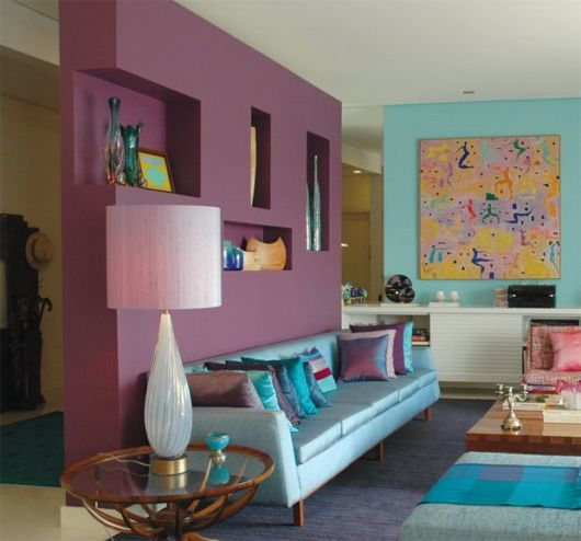 sala bem colorida com elementos azuis e divisória de gesso roxa