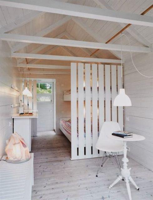 quarto decorado com predominância do branco e divisória rústica