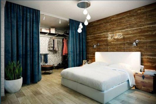 quarto com divisória de cortina azul que leva para o closet