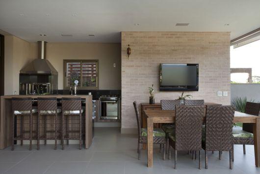 edicula com cozinha e mesa de jantar em tons de marrom e eletros de inox