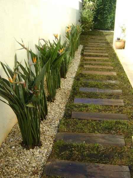 caminho de madeira e rente a parede pedrinhas decorativas com plantas