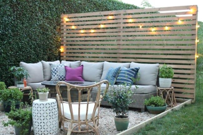 Jardim pequeno com painel de pallets e pedrinhas