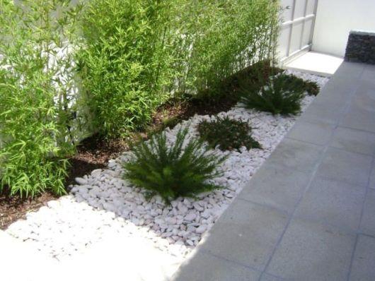 deck em jardim pequeno:As pedras brancas dão destaque a vegetação