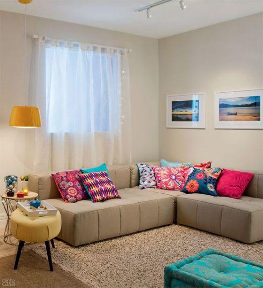 Uma Sala Pequena Decorada ~  Quadro colorido na parede; E no canto do ambiente, uma rede pendurad