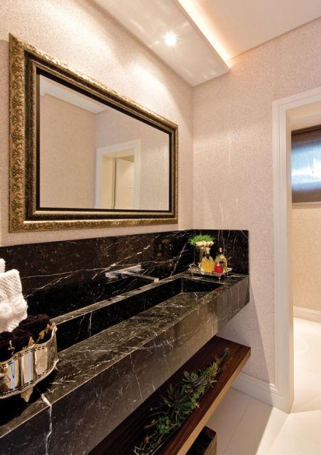 Na parede, espelho com moldura dourada