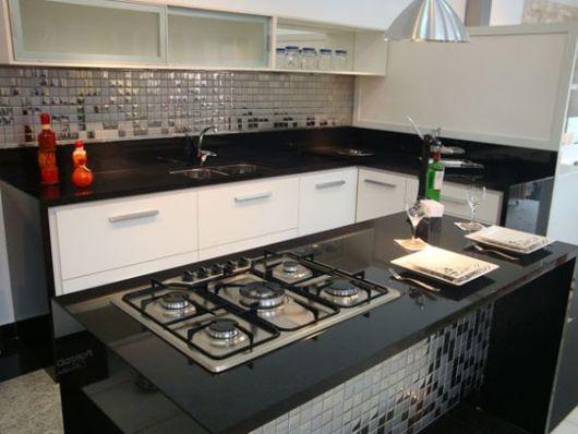 A cozinha pequena tem armários planejados brancos