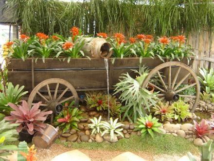 jardim rústico roda de carroça e fonte