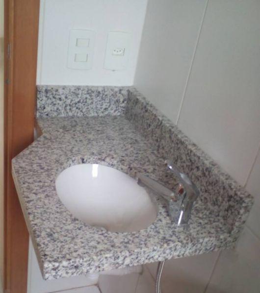 A cuba pequena com bancada em granito fazem parte do projeto do banheiro