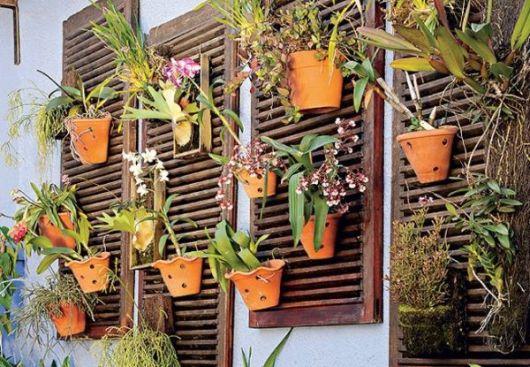 Vasinhos de orquídeas em meio às estruturas de madeira
