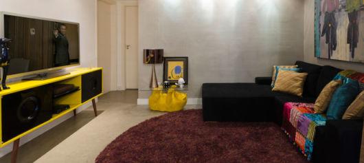 salas com sofá preto com decoração amarela