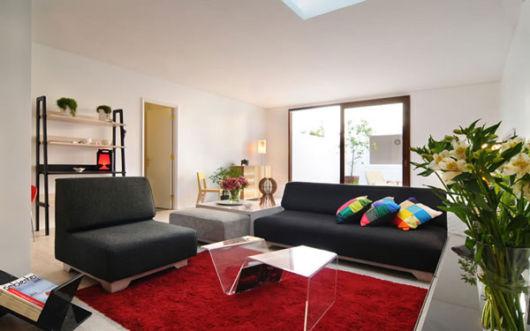 salas com sofá preto com tapete vermelho