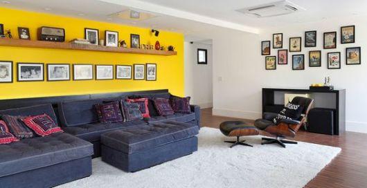 salas com sofá preto parede amarela