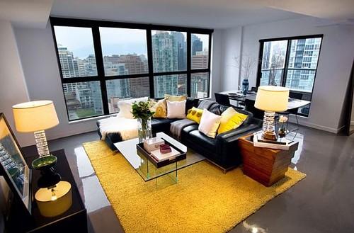 salas com sofá preto tapete amarelo