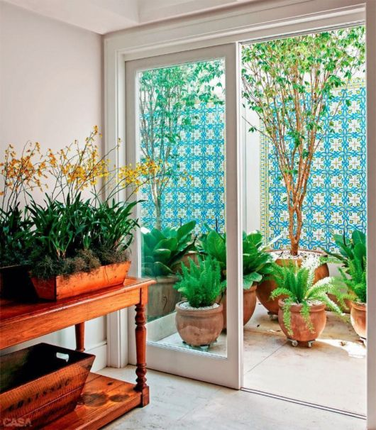 jardim-de-inverno-na-sala-com-porta-de-vidro-e-iluminacao-natural