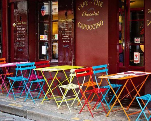 Cadeiras e mesas coloridas do lado de fora da lanchonete.