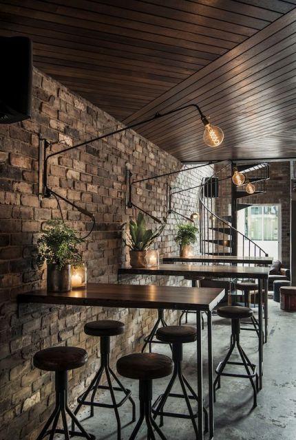 Parede de tijolos e mesas com vasos de planta na decoração.