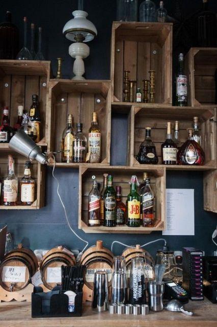 Caixotes pendurados na parede, servindo de nichos para as bebidas.