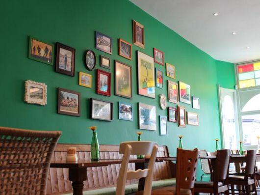 Parede verde com quadros de diversos tamanhos.