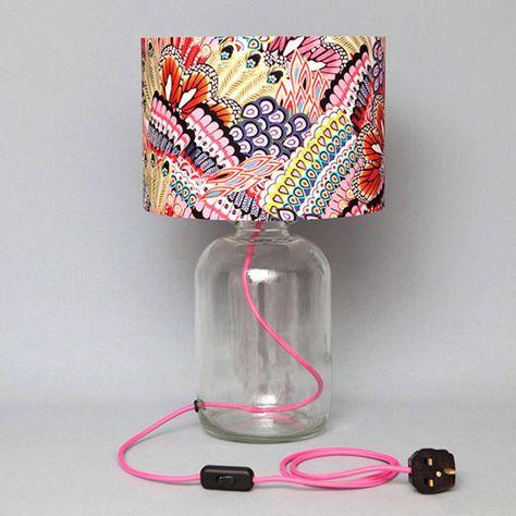 abajur de garrafão de vidro com fio rosa passando por dentro