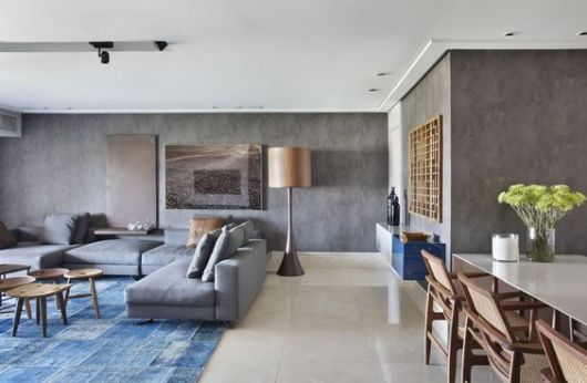 Sala com tapete azul e restante do piso de cerâmica.