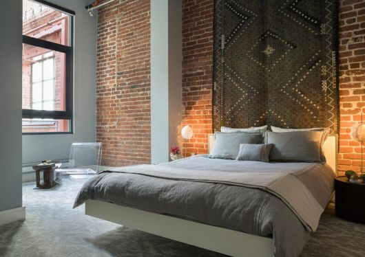 cama flutuante com tapete pendurado na parede ao fundo