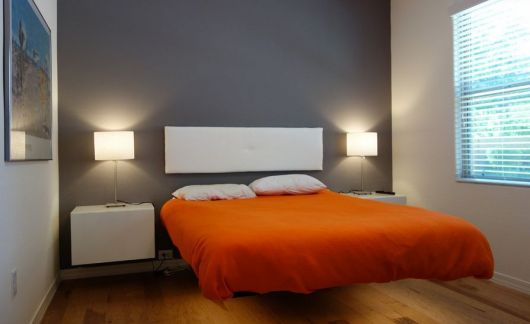 cama flutuante com criados-mudos, ao lado, fixos na parede