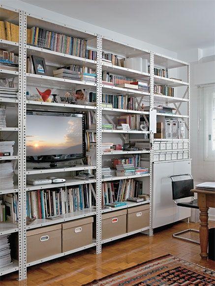 estante de aço em torno da televisão com livros