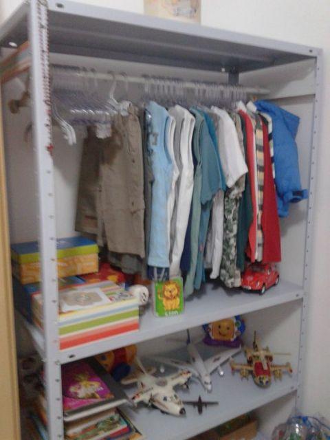 estante de aço no quarto usada como guarda-roupa
