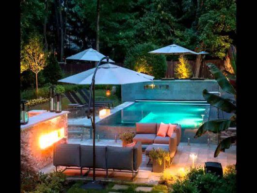 jardim com piscina iluminada e com guarda-sol em volta