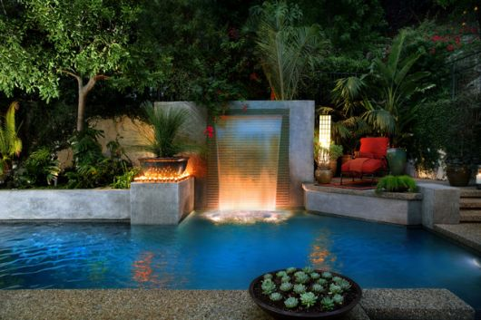 jardim com piscina e cascata iluminada