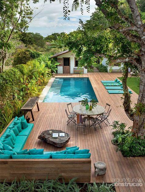 jardim com piscina com deck com sofá, espreguiçadeiras e mesa
