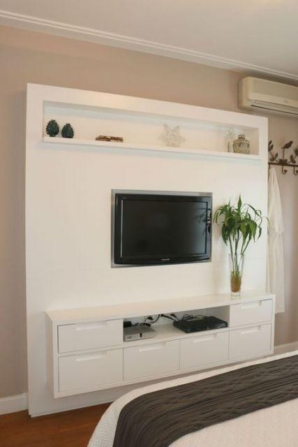 móvel planejado de painel com prateleiras e armários em torno da TV