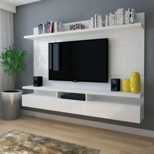 móvel planejado branco de painel com prateleiras e aparador em torno de TV