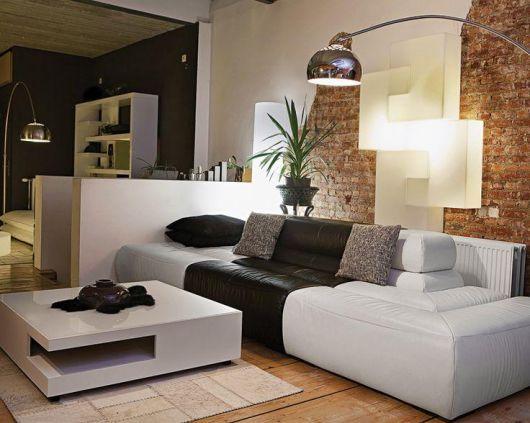 Sala de estar com sofa branco, almofadas pretas e luminaria de chão na cor prata.