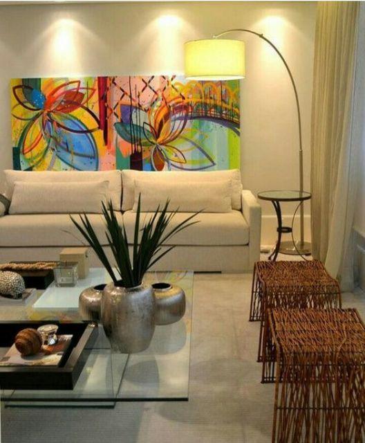 Sala clean com quadro colorido e luminaria de canto com lampada amarela.